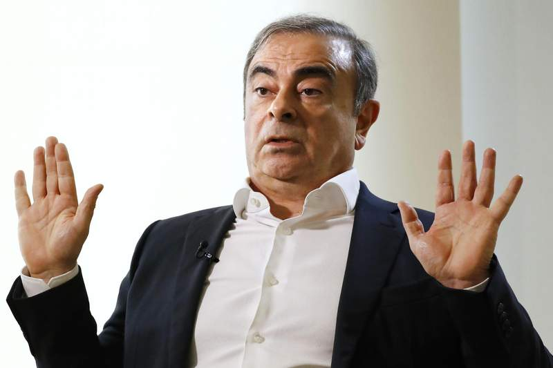 FILE - In this Jan. 10, 2020, file photo, former Nissan Chairman Carlos Ghosn speaks to Japanese media during an interview in Beirut, Lebanon. U.S. authorities have arrested two men accused of helping former Nissan Chairman Carlos Ghosn flee Japan while awaiting trial on charges of financial misconduct. Michael Taylor and his son Peter Taylor were arrested Wednesday by the U.S. Marshals Service on Wednesday morning in Harvard, Massachusetts.  (Meika Fujio/Kyodo News via AP, File)
