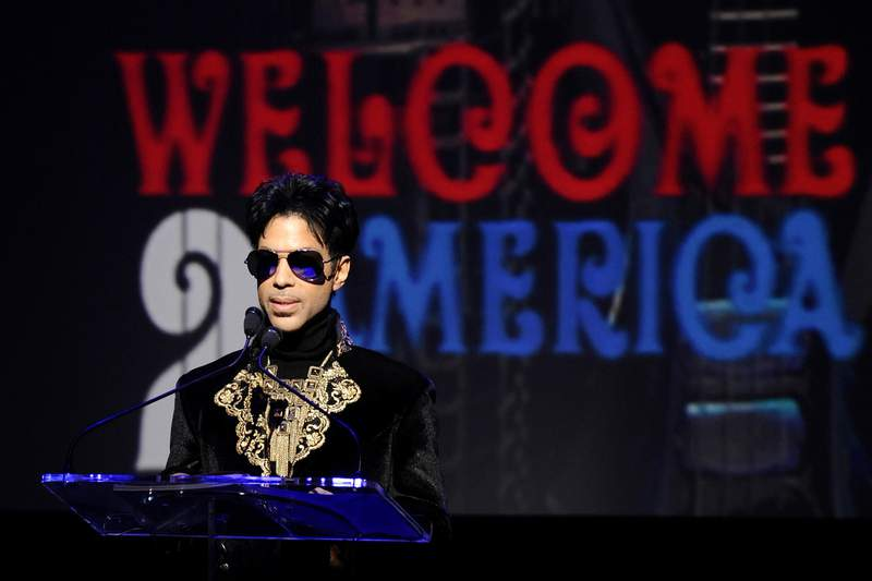 """FILE - In this Oct. 14, 2010 file photo, musician Prince holds a news conference at The Apollo Theater announcing his """"Welcome 2 America"""" tour in New York. The ongoing controversy over the money left behind by Prince when he died without a will is heating up again after Internal Revenue Service calculations showed that executors of the rock star's estate undervalued it by 50%, or about $80 million. (AP Photo/Peter Kramer, File)"""