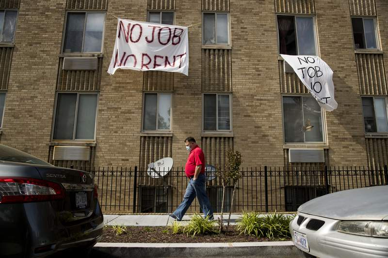 """FILE - In this May 20, 2020 file photo, signs that read """"No Job No Rent"""" hang from the windows of an apartment building in Northwest Washington. Renters are nearing the end of their financial rope as the assistance and protections given to them during the pandemic run their course. About 30% of renters polled by the U.S. Census say they have no confidence or slight confidence in their ability to pay rent next month.  (AP Photo/Andrew Harnik, File)"""