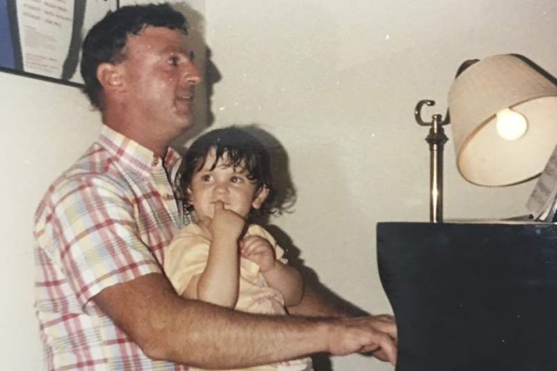 This undated photo provided by the family in May 2020 shows Joseph Policelli at the piano with his niece Stephanie Mayne. At funerals, he made the organ moan, and at weddings, it thundered in joy. On Christmas, bells twinkled; on Easter, trumpets blasted. He delivered victorious graduation marches and bellowing birthday celebrations, blaring the pipes and vibrating the pews every Sunday in between. He was unassuming, egoless and largely anonymous, but in the lives of generations of Catholics in communities around Massachusetts, Policelli played the soundtrack. He died from COVID-19 on April 27, 2020 at 71. (Family photo via AP)