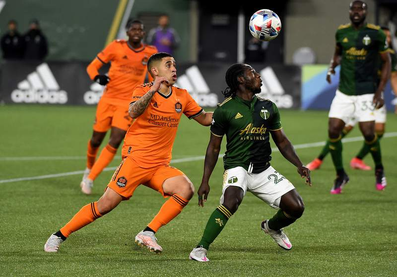 PORTLAND, OREGON - APRIL 24: Matias Vera #22 of Houston Dynamo and Yimmi Chara #23 of Portland Timbers go after a ball during the first half of the match at Providence Park on April 24, 2021 in Portland, Oregon. The Timbers won 2-1. (Photo by Steve Dykes/Getty Images)