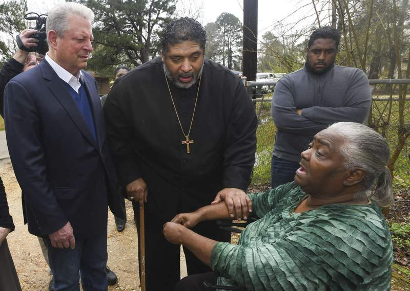 FILE - In this Feb. 21, 2019, file photo, former Vice President Al Gore, left, founder of the Climate Reality Project, and the Rev. William Barber II, president of the Repairers of the Breach, visit Lowndes County resident Charlie Mae Holcombe to talk about the failing wastewater sanitation system at her home in Hayneville, Ala. An anti-poverty coalition led by Barber is scheduled to hold a virtual march Saturday. The Mass Poor Peoples Assembly & Moral March on Washington aims to build upon the nations principles to pursue solutions to poverty  something advocates say is getting especially severe in rural areas. (AP Photo/Julie Bennett, File)