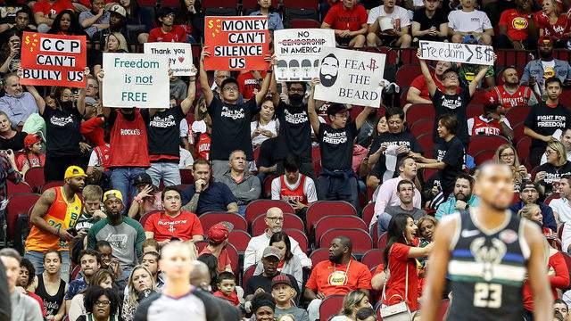 Protesters hold signs during the game between the Houston Rockets and the Milwaukee Bucks at Toyota Center on October 24, 2019, in Houston.