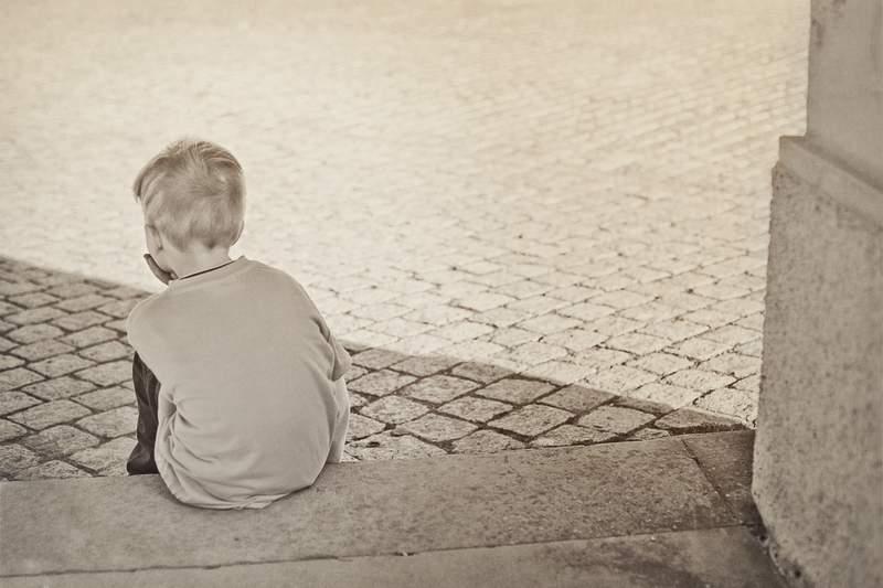 A boy sits alone.
