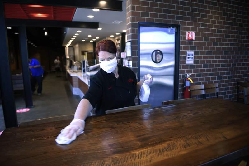 Shannon Hambrick wipes down counters at the post-coronavirus opened Cheeseburger Bobby's restaurant in Martinez, Ga., Monday, April 27, 2020. (Michael Holahan/The Augusta Chronicle via AP)