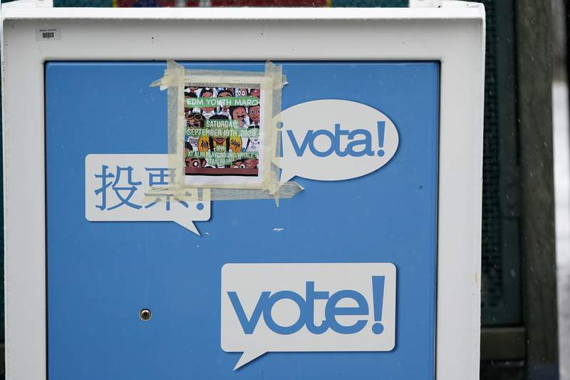 A poster for a youth march is pasted to the side of a King County ballot drop box, closed until ballots are mailed about three weeks before the election, on a Seattle street Thursday, Sept. 24, 2020. (AP Photo/Elaine Thompson)