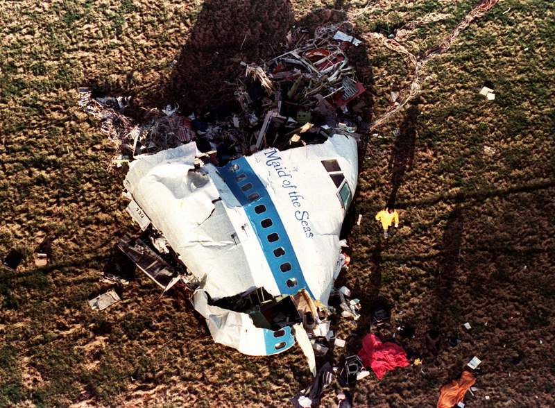 In this Dec. 22, 1988, file photo police and investigators look at what remains of the nose of Pan Am 103 in a field in Lockerbie, Scotland. The Justice Department expects to unseal charges in the coming days in connection with the 1988 bombing of a Pan Am jet that exploded over Lockerbie, Scotland, killing 270 people, according to a person familiar with the case. (AP Photo/Martin Cleaver, File)