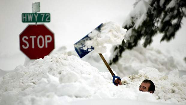 """THIRD DAY OF MARCH BLIZZARD--3-20-2002--Neal Nixon of Coal Creek digs a pathway to his car near the intersection of Colorado Highway 72 and Twin Spruce Rd. in Coal Creek Canyon Thursday. Nixon was trying to free up his Kia Sephia sedan which was totally buried under snow so he could take his mother, Lori, to her wedding in Las Vegas on Saturday. """"She's pretty freaked out,"""" admits Nixon. POST STAFF PHOTO BY GLENN ASAKAWA  (Photo By Glenn Asakawa/The Denver Post via Getty Images)"""