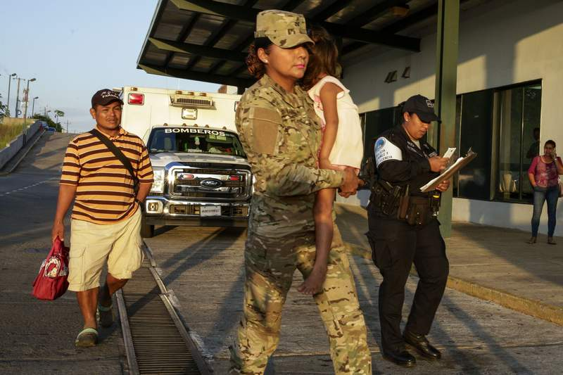 """Jose Gonzalez, left, follows his 5-year-old daughter, carried by a police officer, as they leave a hospital in Santiago, Panama, Thursday, Jan. 16, 2020. Gonzalez's wife and five of their children are among seven people killed in a religious ritual in the Ngabe Bugle indigenous community. According to local prosecutor Rafael Baloyes indigenous residents were rounded up by lay preachers and tortured, beaten, burned and hacked with machetes to make them """"repent their sins."""" (AP Photo/Arnulfo Franco)"""