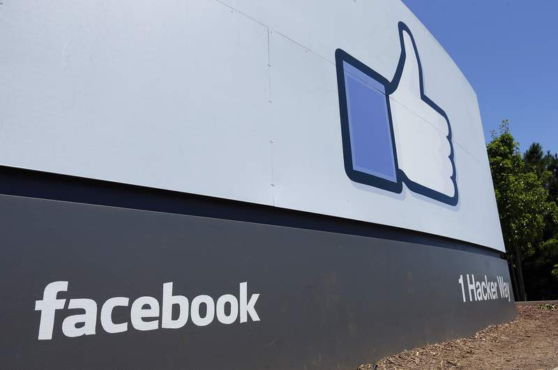 FILE - This July 16, 2013 file photo shows a sign at Facebook headquarters in Menlo Park, Calif. Beginning Thursday, Aug. 13, 2020 U.S. Facebook users who post about voting may start seeing an addendum to their messages -- labels directing readers to authoritative information about the upcoming presidential election. It's the social network's latest step to to combat election-related misinformation on its platform as the Nov. 3 election nears  one in which many voters may be submitting ballots by mail for the first time. (AP Photo/Ben Margot, File)