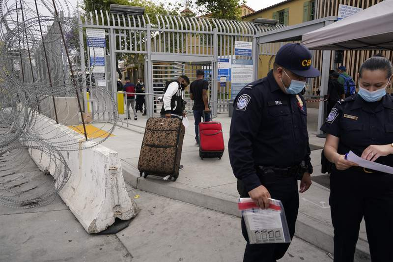 FILE - In this July 5, 2021 file photo, Honduran Alex Cortillo, left, and his stepbrother pull their suitcases to the border crossing into the U.S. to begin the asylum process, in Tijuana, Mexico. Mexicos President Andrs Manuel Lpez Obrador sidestepped questions on Aug. 26, 2021 about the reinstatement of the U.S. Remain in Mexico policy that forces people to wait in Mexico for hearings on asylum claims. (AP Photo/Gregory Bull, File)