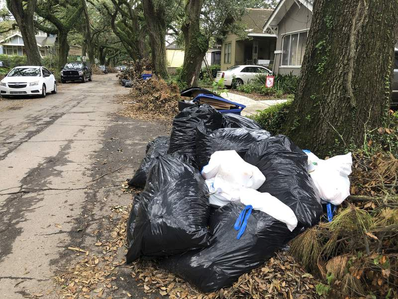 Bags and containers of household garbage and piles of storm debris line a New Orleans street, Friday, Sept. 17, 2021. Nearly three weeks after Hurricane Ida struck the city, many residents are growing angry at the lack of garbage pickups in New Orleans— a problem officials say stems from labor shortages that began with the COVID-19 pandemic and were made worse by the storm. (AP Photo/Kevin McGill)