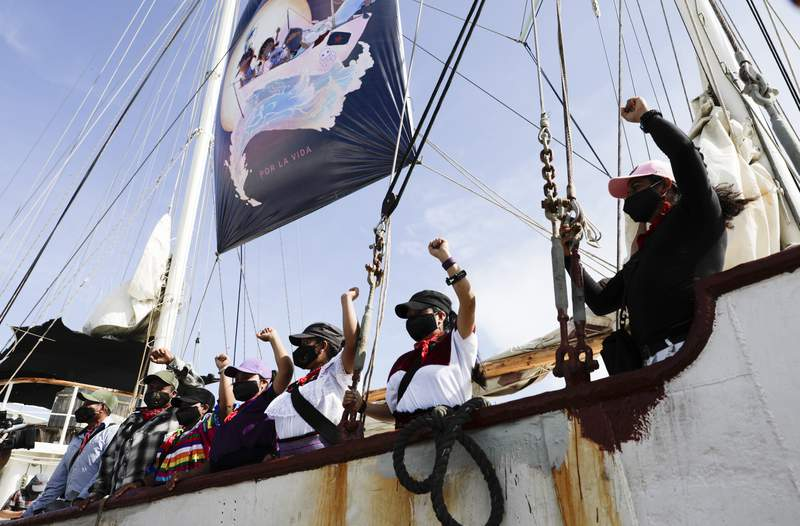 """A delegation of the Zapatista Army of National Liberation, EZLN, say goodbye from a ship as they depart to Europe from Isla Mujeres, Quintana Roo state, Mexico, Sunday, May 2, 2021. The rebel delegation says they are planning the trip to """"invade"""" Spain, as Mexico marks the anniversary of its 1519-1521 Spanish Conquest. (AP Photo/Eduardo Verdugo)"""