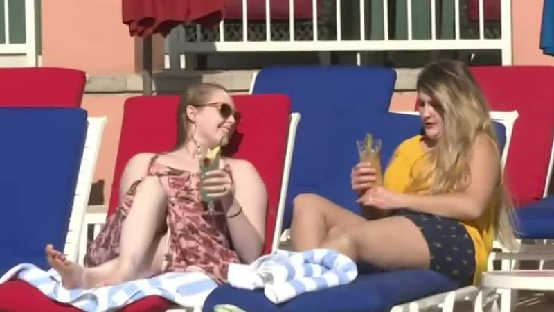 Two women hang out by the pool at Moody Gardens.