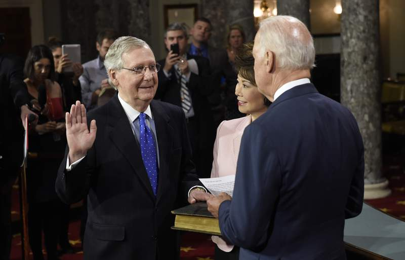 FILE - In this Jan. 6, 2015, file photo, then-Vice President Joe Biden, right, administers the Senate oath to Senate Majority Leader Mitch McConnell of Ky. during a ceremonial re-enactment swearing-in ceremony in the Old Senate Chamber on Capitol Hill in Washington. McConnell's wife, Elaine Chao is at center. President Joe Bidens sit-down on May 12, 2021, with Senate Republican leader Mitch McConnell and other congressional leaders comes as the White House accelerates its efforts to reach a bipartisan infrastructure agreement, or at least aims to show its trying.  (AP Photo/Susan Walsh, File)