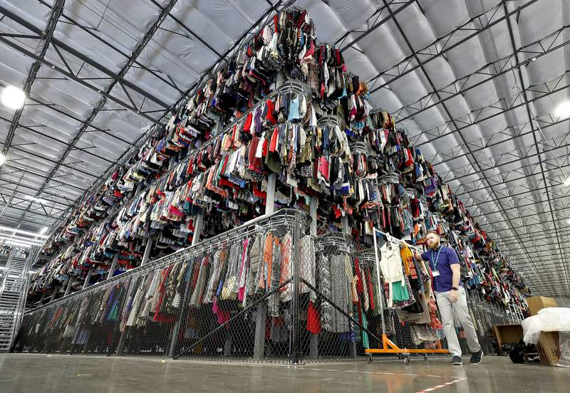 FILE - In this March 12, 2019, file photo thousands of garments are stored on a three-tiered conveyor system at the ThredUp sorting facility in Phoenix.  Shares of ThredUp rose 30% in their stock market debut Friday, March 26, 2021, reflecting investor enthusiasm for the online marketplace for second-hand fashion goods.  (AP Photo/Matt York, File)