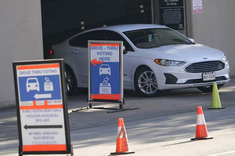 FILE  In this Nov. 3, 2020, file photo a car leaves a drive-thru voting site on Election Day in Houston. As Texas moves ahead with a push to tighten voting laws, Republican lawmakers have zeroed in on Houston and surrounding Harris County. The effort is one of the clearest examples of how the GOP's nationwide campaign to impose new voting restrictions can target Democrats, even as they insist the measures are not partisan. (AP Photo/David J. Phillip, File)