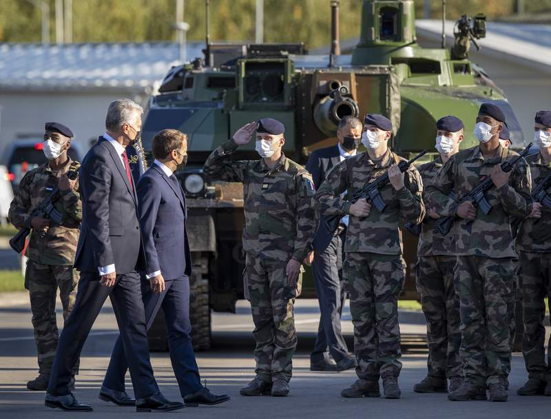Lithuania's President Gitanas Nauseda, left, and French President Emmanuel Macron inspect French soldiers of the NATO enhanced forward presence battalion during their visit to the Rukla military base some 100 kms (62.12 miles) west of the capital Vilnius, Lithuania, Tuesday, Sept. 29, 2020. (AP Photo/Mindaugas Kulbis)