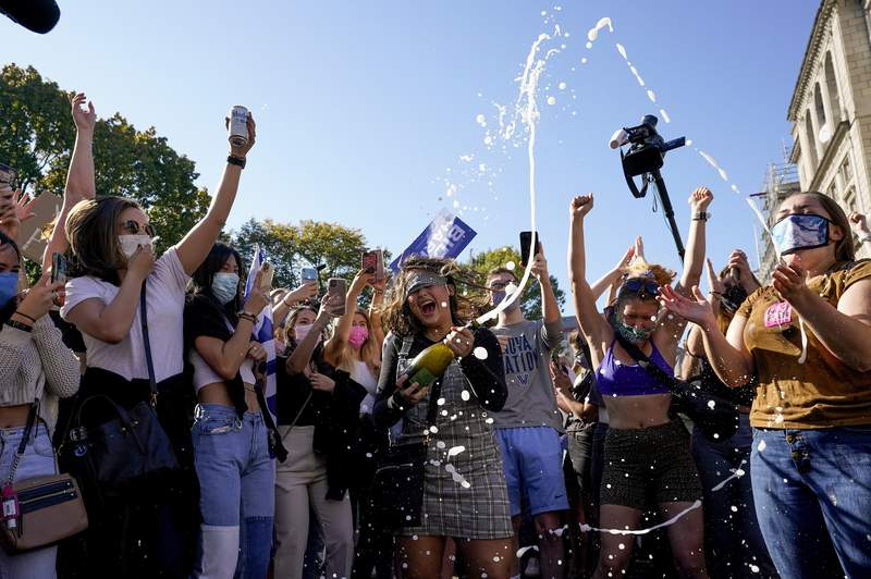 Amanda Madden sprays champagne as people celebrate at Black Lives Matter Plaza after CNN called the race in favor of Democratic presidential candidate Joe Biden over Pres. Donald Trump to become the 46th president of the United States, Saturday, Nov. 7, 2020, in Washington.  (AP Photo/Alex Brandon)