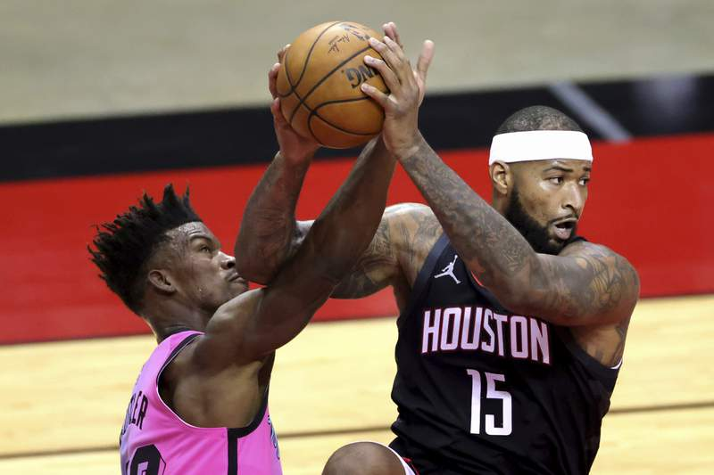 Houston Rockets' DeMarcus Cousins, right, gets possession of the ball next to Miami Heat's Jimmy Butler during the first quarter of an NBA basketball game Thursday, Feb. 11, 2021, in Houston. (Carmen Mandato/Pool Photo via AP)