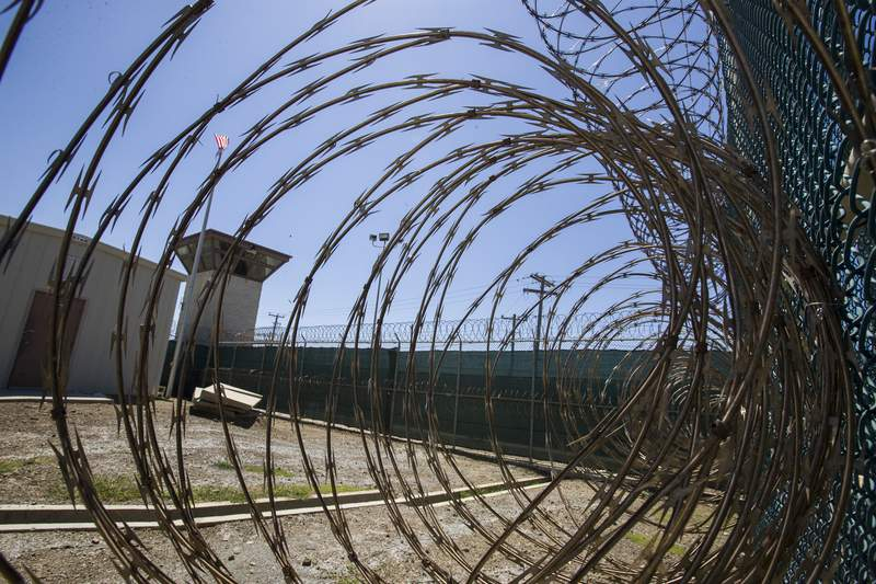 FILE - In this Wednesday, April 17, 2019 file photo reviewed by U.S. military officials, the control tower is seen through the razor wire inside the Camp VI detention facility in Guantanamo Bay Naval Base, Cuba.  The U.S. is backing off for now on a plan to offer COVID-19 vaccinations to the 40 prisoners held at the detention center at Guantanamo Bay, Cuba.Pentagon chief spokesman John Kirby said in a tweet Saturday, Jan. 30, 2021 that the Defense Department would be pausing the plan to give the vaccination to those held at Guantanamo while it reviews measures to protect troops who work there. (AP Photo/Alex Brandon, File)