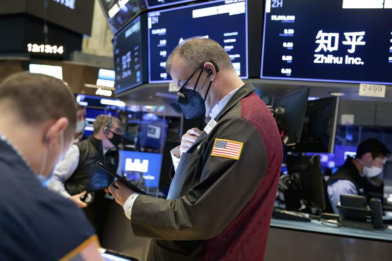In this photo provided by the New York Stock Exchange, William Lawrence, center, works with fellow traders on the floor, Friday, March 26, 2021. Stocks rose in afternoon trading on Wall Street Friday with technology companies and banks leading the way higher. (Nicole Pereira/New York Stock Exchange via AP)