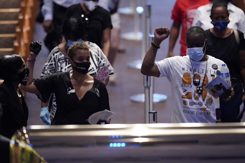 Mourners raise fists by the casket bearing the remains of George Floyd at a public visitation at the Fountain of Praise church June 8, 2020, in Houston, Texas. Floyd died after being restrained by Minneapolis police officers on May 25.  (Photo by David J. Phillip-Pool/Getty Images)