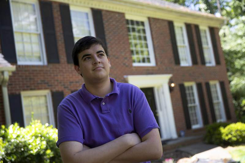 College student Jake Mershon poses in front of his parents home Thursday, May 7, 2020, in Roswell Ga. Mershon, who just finished his sophomore year at Florida State University in Tallahassee, moved back in with his mother, her fiance and his sister in Atlanta after on-campus classes shut down in mid-March. His mother included him on the census form for her household, and neither Mershon nor his three other roommates filled out a questionnaire for their Tallahassee apartment. (AP Photo/John Bazemore)