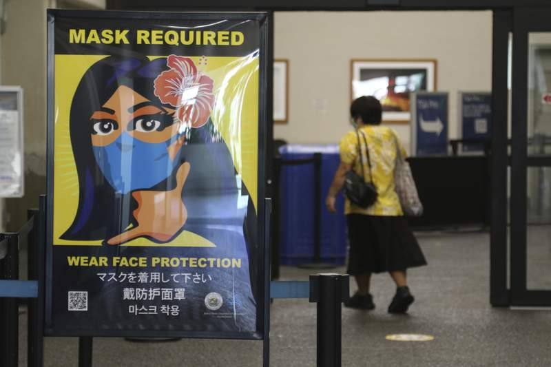 FILE - In this Oct. 2, 2020 file photo, a woman walks into the international airport in Honolulu amid a quarantine rule that effectively shut down the tourism industry in the state. A requirement that people on planes and other forms of transportation in the U.S. wear masks to prevent the spread of COVID-19 will remain in place through at least Sept. 13, the Transportation Security Administration said Friday, April 30, 2021 (AP Photo/Caleb Jones, File)
