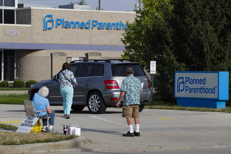 FILE - In this Aug. 16, 2019 file photo, abortion protesters attempt to handout literature as they stand in the driveway of a Planned Parenthood clinic in Indianapolis. A federal judge has blocked a new Indiana law that would require doctors to tell women undergoing drug-induced abortions about a disputed treatment for potentially stopping the abortion process. The ruling Wednesday, June 30, 2021,  came just before the so-called abortion reversal law adopted by Indianas Republican-dominated Legislature was to take effect Thursday.  (AP Photo/Michael Conroy)