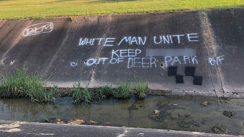 Racist graffiti is seen scrawled on a cement creek bank in this image released by the Deer Park Police Department on Aug. 11, 2020.