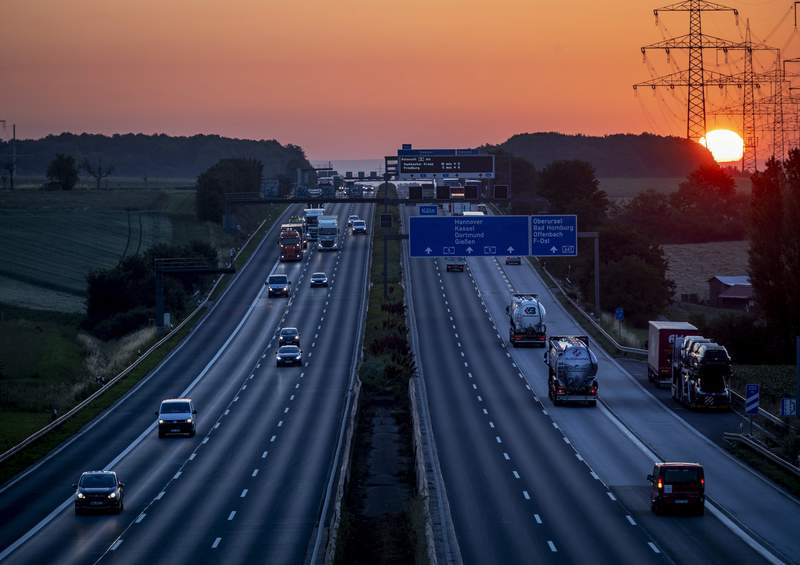Cars and trucks are seen on a highway as the sun rises in Frankfurt, Germany, Tuesday, June 23, 2020. (AP Photo/Michael Probst)