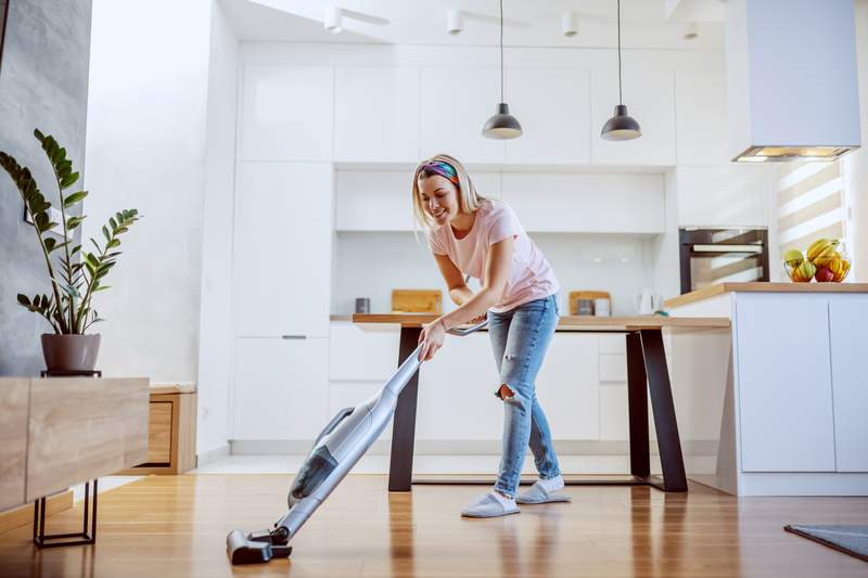 Smiling worthy Caucasian blond housewife dressed casual using steamer to clean parquet in her apartment.