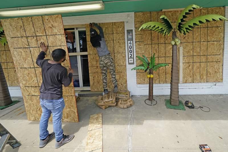 Issac Alvarado, right, and Kevin Enriquez board up windows on coastal decor store Bayside Chic, Tuesday, Aug. 25, 2020, in Galveston, Texas, as Hurricane Laura heads toward the Gulf Coast. (AP Photo/David J. Phillip)