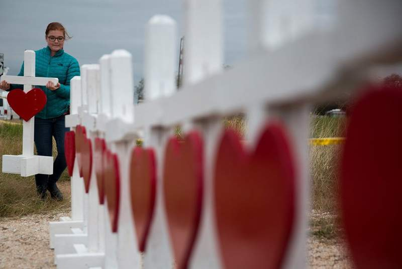 Hannah Krueger adds a cross to a memorial near the First Baptist Church in Sutherland Springs onNov. 8, 2017, three days after 23 churchgoers were killed in a mass shooting there.