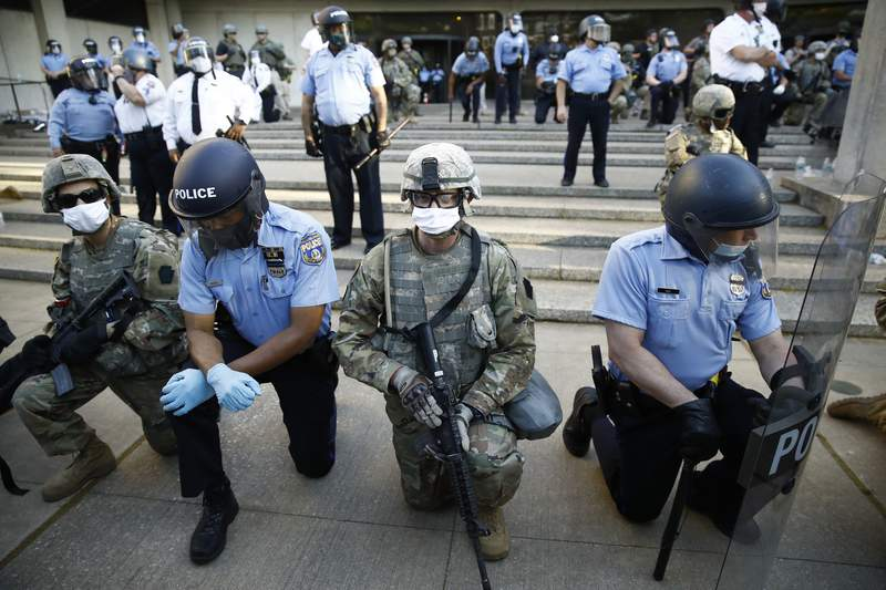 FILE - In this June 1, 2020, file photo, Philadelphia police and Pennsylvania National Guard take a knee at the suggestion of Philadelphia Police Deputy Commissioner Melvin Singleton, unseen, outside Philadelphia Police headquarters in Philadelphia, during a march calling for justice over the death of George Floyd. If the military has any role in next week's election, it most likely will involve National Guard members under state control  not troops on federal duty.  (AP Photo/Matt Rourke, File)