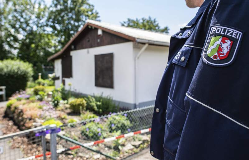 During the investigation of serious sexual abuse of children, a police officer is standing in front of the arbour where the presumed main perpetrator placed parts of his server system, in Muenster, Germany, Saturdau, June 6, 2020. The investigators found hard disks and video cameras among other things. (Guido Kirchner/dpa via AP)