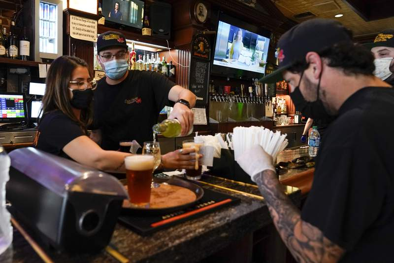FILE - In this May 29, 2020, file photo, Jessica Ciaramitaro, Daryn Feenstra and Nicholas Soriano mix drinks while wearing face masks at the bar at San Pedro Brewing Company in the San Pedro area of Los Angeles. Coronavirus cases are rising in nearly half the U.S. states, as states are rolling back lockdowns. (AP Photo/Ashley Landis, File)