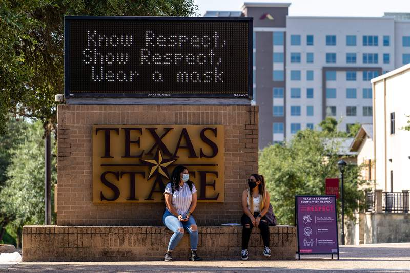 Two students sit under a sign encouraging students to wear a mask on the first day of classes for the fall semester at Texas State University in San Marcos on Aug. 24, 2020.