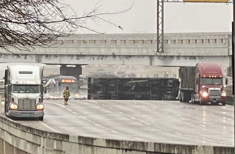 Officials are cleaning up a crash scene after an 18-wheeler that appears to have been carrying boxes of bees rolled over at the Finesilver Curve near downtown. (Courtesy of KSAT)
