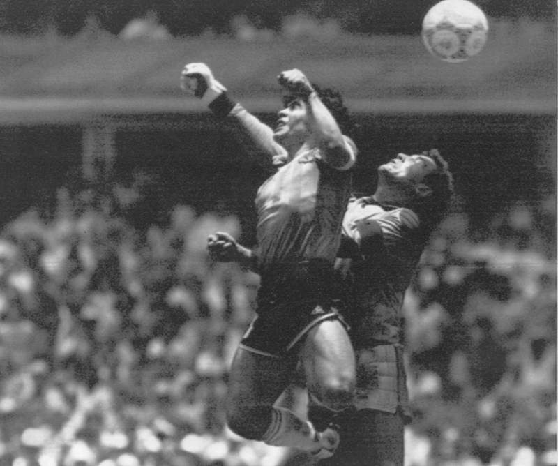 """FILE - In this June 22, 1986 file photo, Argentina's Diego Maradona, left, beats England's goalkeeper Peter Shilton to a high ball and scores his first of two goals at the World Cup quarterfinal soccer match in Mexico City. On this day: This was the day of the """"Hand of God,"""" when Maradona used his left fist to knock a ball past England's Shilton. (El Grafico via AP, File)"""