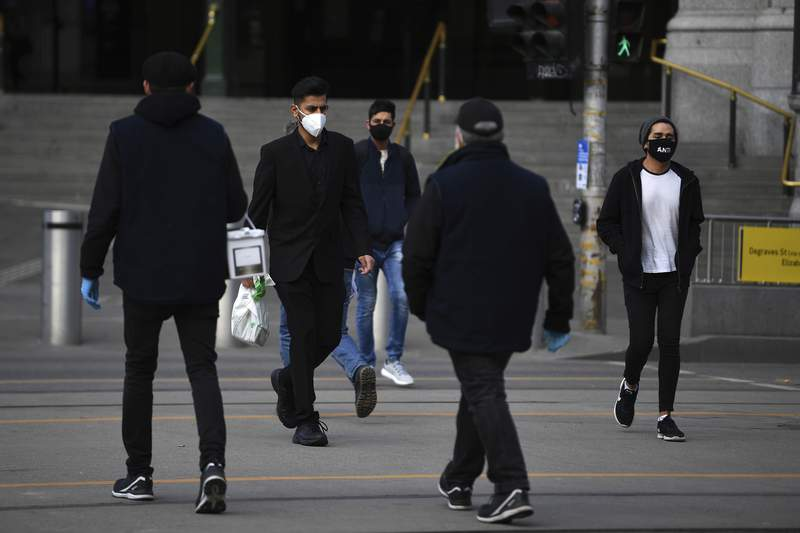 People wearing face masks to help protect against the spread of the new coronavirus walk outside Flinders Street Station in Melbourne, Australia, Thursday, July 23, 2020. There were few bare faces among rush-hour commuters in Australias second-largest city on Thursday morning as Melbourne residents were largely complying with a new law making face coverings compulsory. (James Ross/AAP Image via AP)