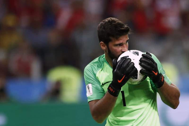 FILE - In this Wednesday, June 27, 2018 file photo, Brazil goalkeeper Alisson kisses the ball after makes a save during their World Cup soccer match against Serbia. There will be no more kissing the ball for good luck in South American soccer. Forget about exchanging jerseys and even spitting or blowing noses on the field also. The soccer governing body of soccer in the region has released a series of specific regulations amid the coronavirus pandemic to protect everyones health when the Copa Libertadores eventually resumes. There is no date set for when the tournament will restart. (AP Photo/Matthias Schrader)