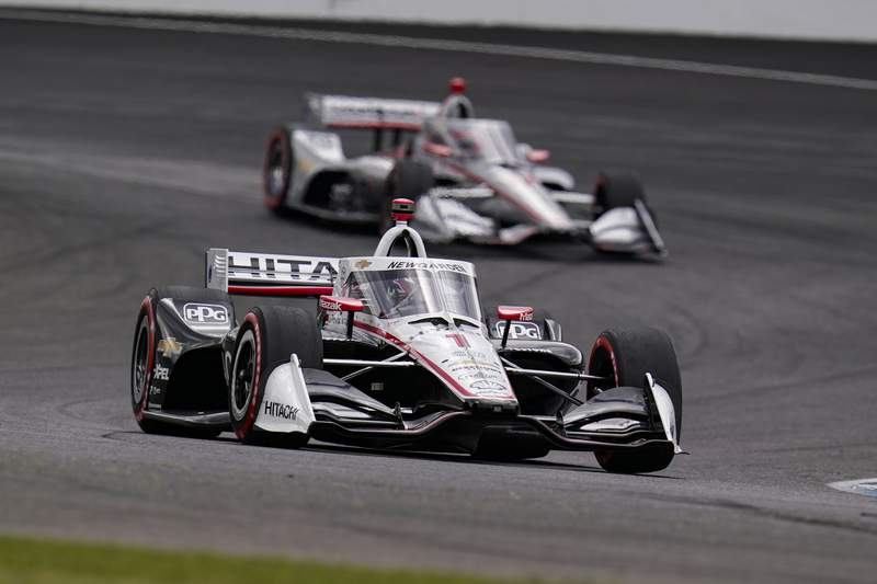 Josef Newgarden leads Will Power, of Australia, through a turn during an IndyCar auto race at Indianapolis Motor Speedway in Indianapolis, Friday, Oct. 2, 2020. (AP Photo/Michael Conroy)