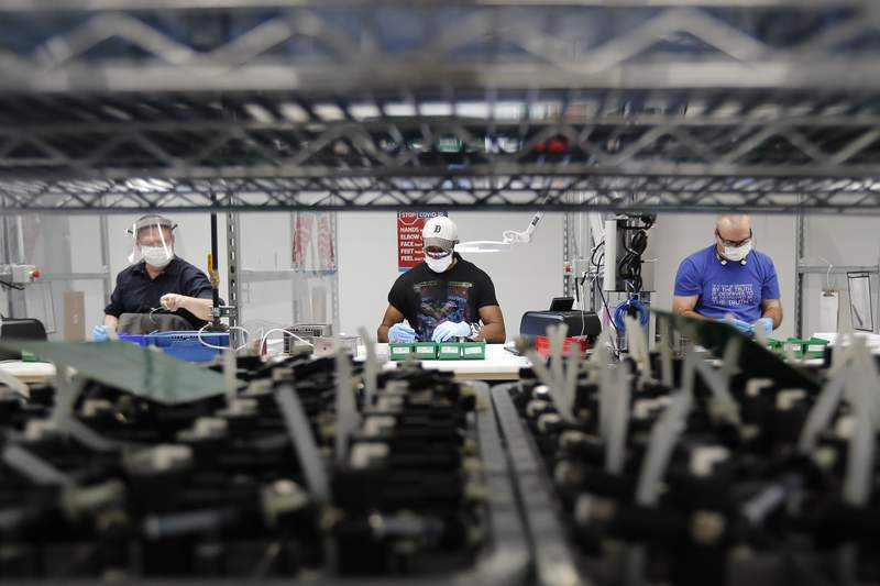 FILE - In this May 13, 2020, file photo, Ford Motor Co., line workers put together ventilators that the automaker is assembling at the Ford Rawsonville plant in Ypsilanti Township, Mich. American industry rebounded last month as factories began to reopen for the first time since being shut down by the coronavirus in Aprll. The Federal Reserve said Tuesday, June 16, 2020, that industrial production  including output at factories, mines and utilities  rose 1.4% in May after plummeting a record 12.4% in April and 4.6% in March. (AP Photo/Carlos Osorio, File)