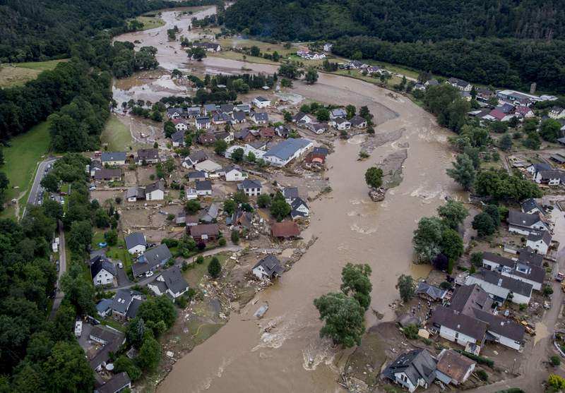 FILE - In this July 15, 2021 file photo the Ahr river floats past destroyed houses in Insul, Germany. Due to heavy rain falls the Ahr river dramatically went over the banks the evening before.  The German government on Wednesday denounced attempts by some people or groups to spread disinformation in areas devastated by floods two weeks ago. (AP Photo/Michael Probst, file)
