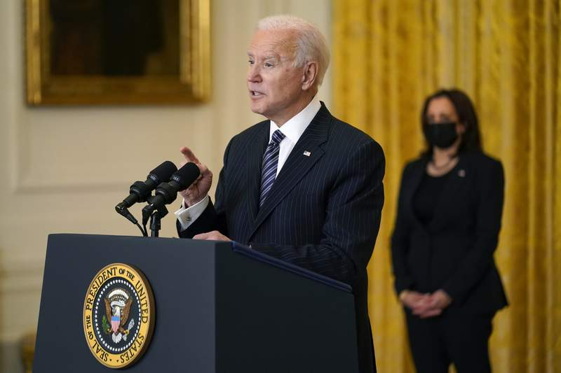 President Joe Biden speaks about COVID-19 vaccinations, from the East Room of the White House, Thursday, March 18, 2021, in Washington, as Vice President Kamala Harris listens. (AP Photo/Andrew Harnik)