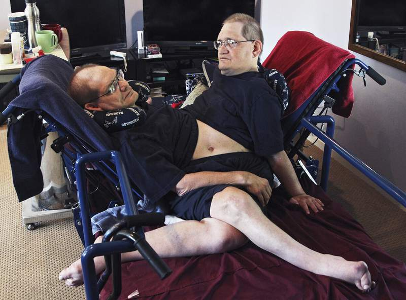 FILE - Donnie, left, and Ronnie Galyon sit inside their Beavercreek, Ohio, home, in a Wednesday, July 2, 2014 file photo. The worlds longest surviving conjoined twins died on July 4, 2020 at the age of 68. Ronnie and Donnie Galyon of Beavercreek, Ohio were born joined at the abdomen. In 2014, earned the distinction of being the worlds oldest set of conjoined twins shortly before their 63rd birthday. (Drew Simon/Dayton Daily News via AP, File)