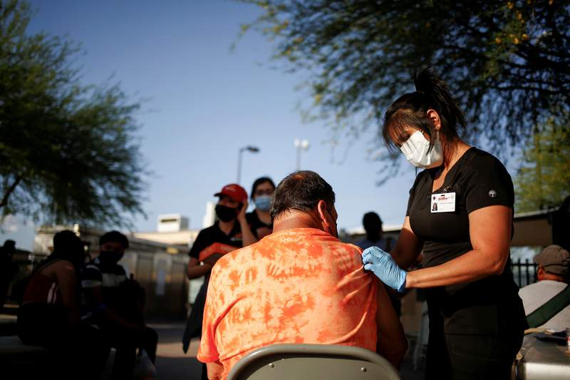 A healthcare worker from the El Paso Fire Department administers the a COVID-19 vaccine at a vaccination center near the Santa Fe International Bridge, in El Paso on May 7, 2021.