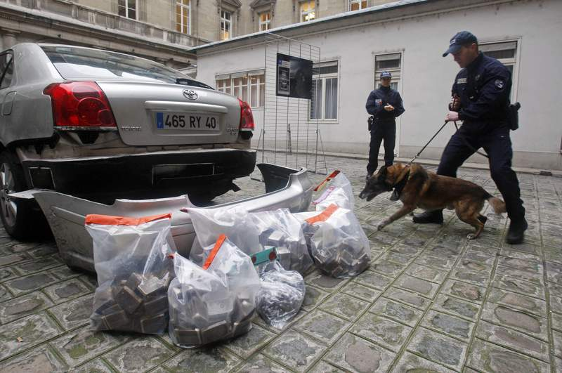 FILE- In this Jan. 15, 2020, file photo, police officers and a police sniffer dog stand next to 63 kilos of marijuana which where found in the car seen left, during a press conference in Paris. France's government launched a two-year nationwide experiment with medical cannabis with a view to eventual legalization. (AP Photo/Michel Euler, File)